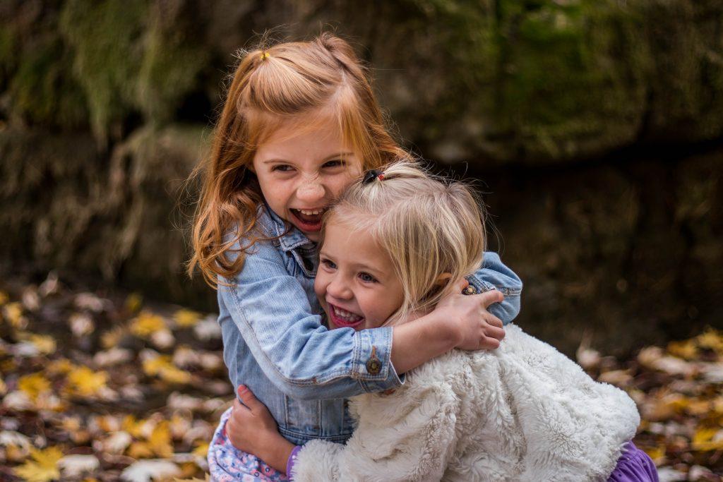 Twee kinderen die elkaar een knuffel geven.